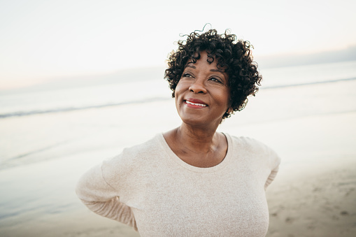 A mature woman smiling on the beach